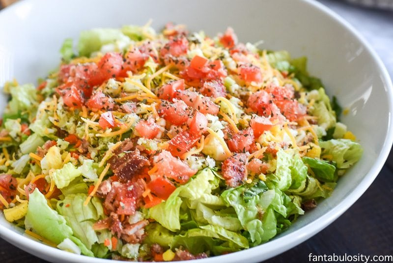 Side Salad with bacon, cheese, tomatoes, romaine lettuce in a white bowl