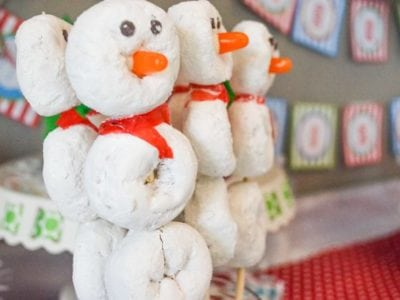 White powdered donuts on a stick with candy to make snowmen