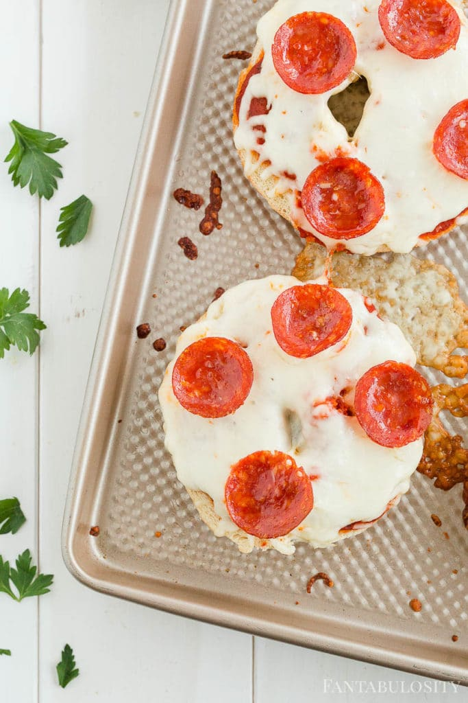 Pizza bagels with pepperoni on a baking sheet