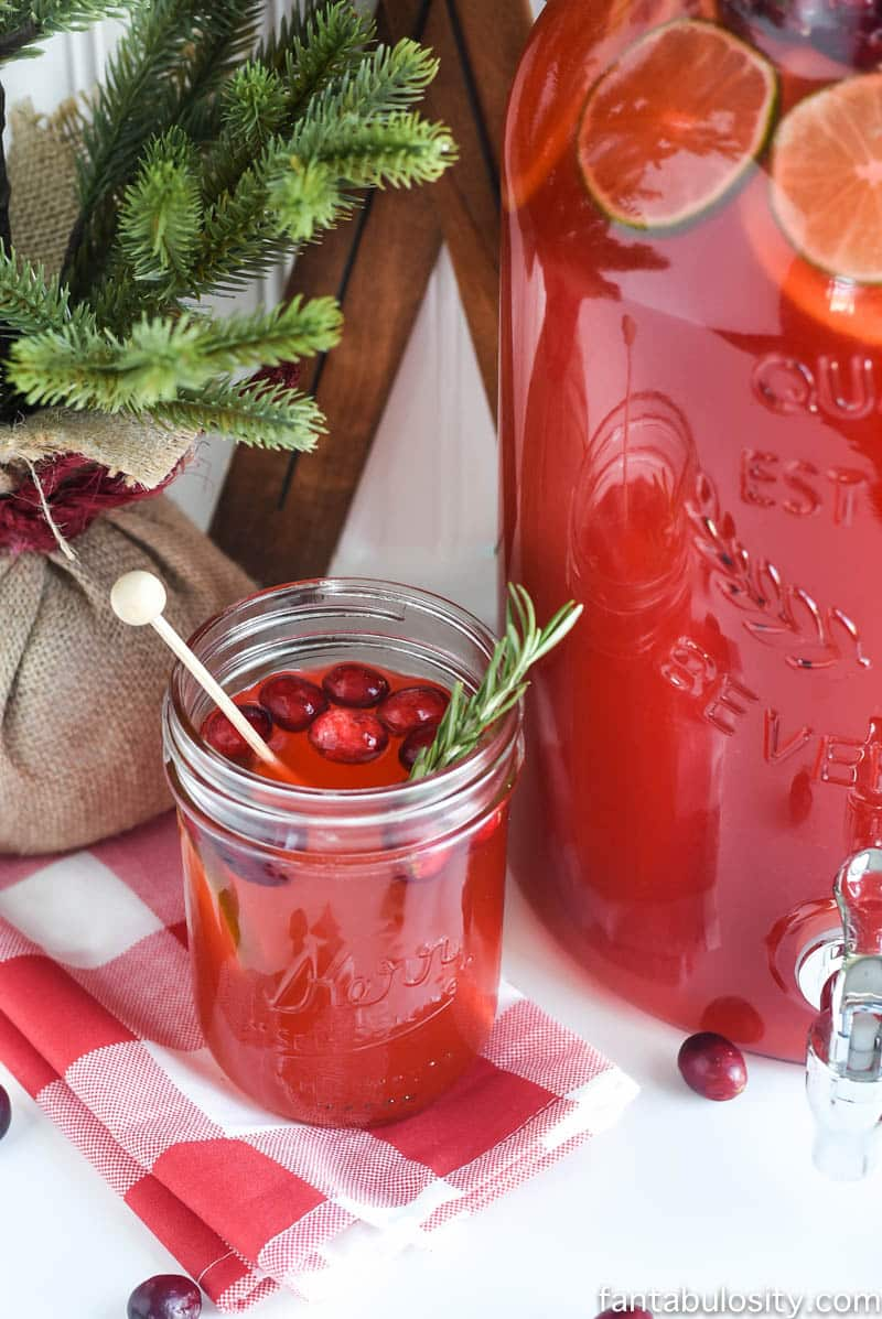 Fruit punch in a mason jar with cranberries and rosemary sprig