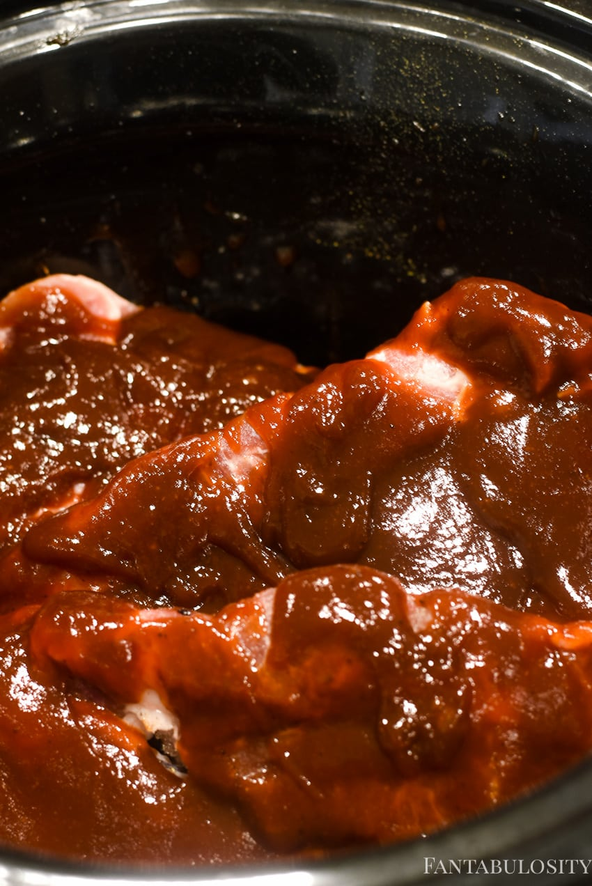 bbq sauce poured on top of raw pork steaks in slow cooker