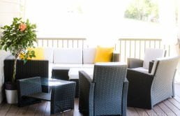 Back patio with white cushions, yellow pillows! Craftsman style home