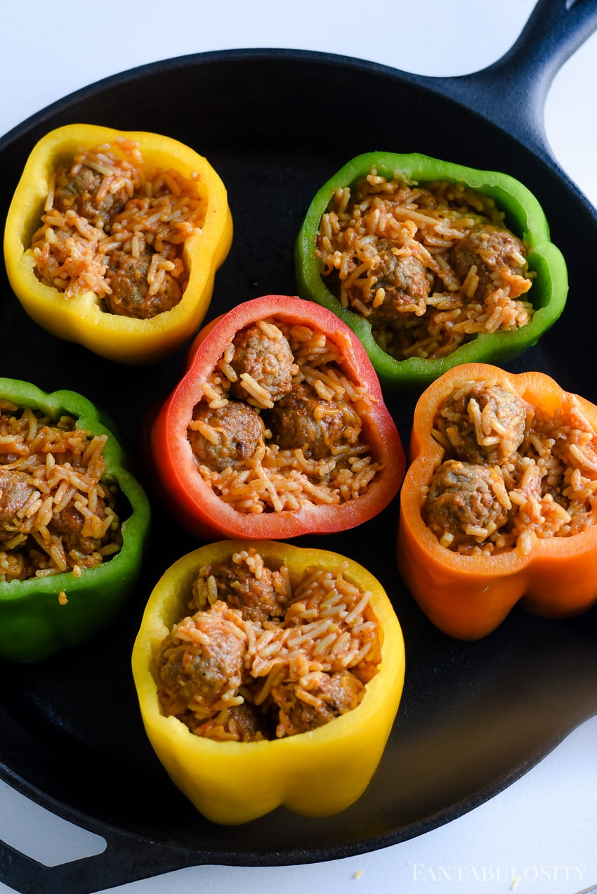 Stuffed peppers recipe, using bell peppers and baking in a cast iron pan. Cheese, rice and meatballs.