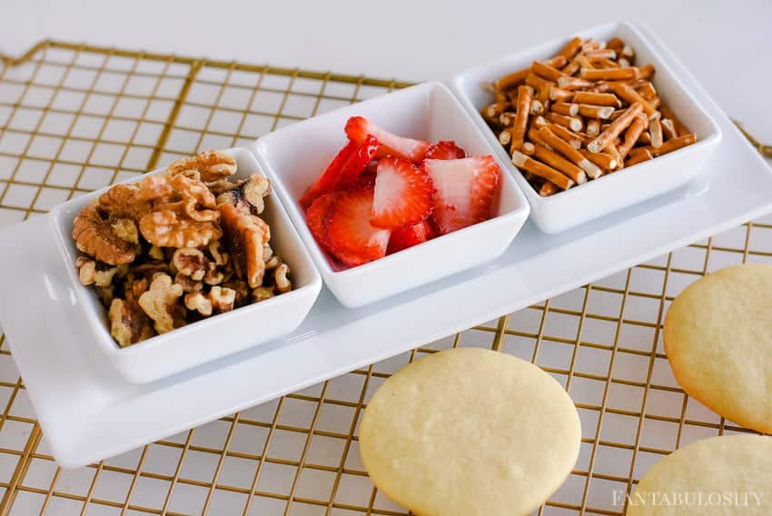 Strawberries, walnuts, and pretzels on top of sugar cookies