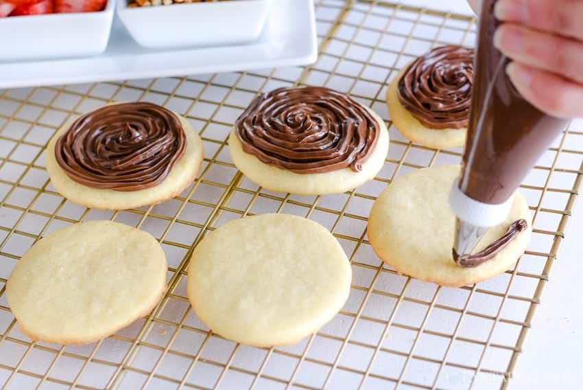 Top the sugar cookies with Nutella and other toppings