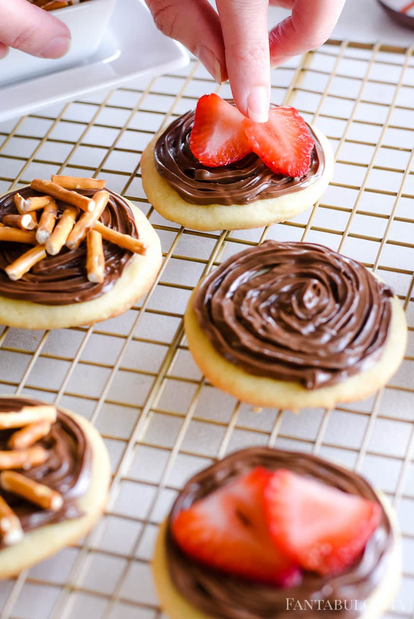 Place sliced strawberries on top of the sugar cookies with Nutella