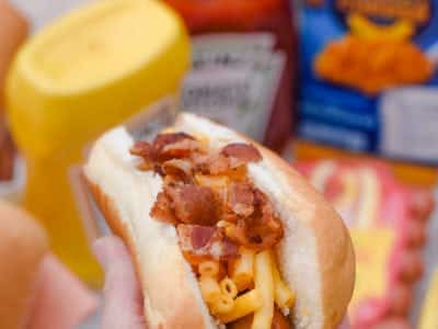 Hot dog with mac and cheese with crumbled bacon