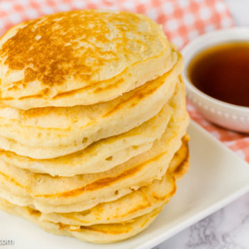 Pancakes from scratch recipe, stacked on a plate with syrup in a bowl