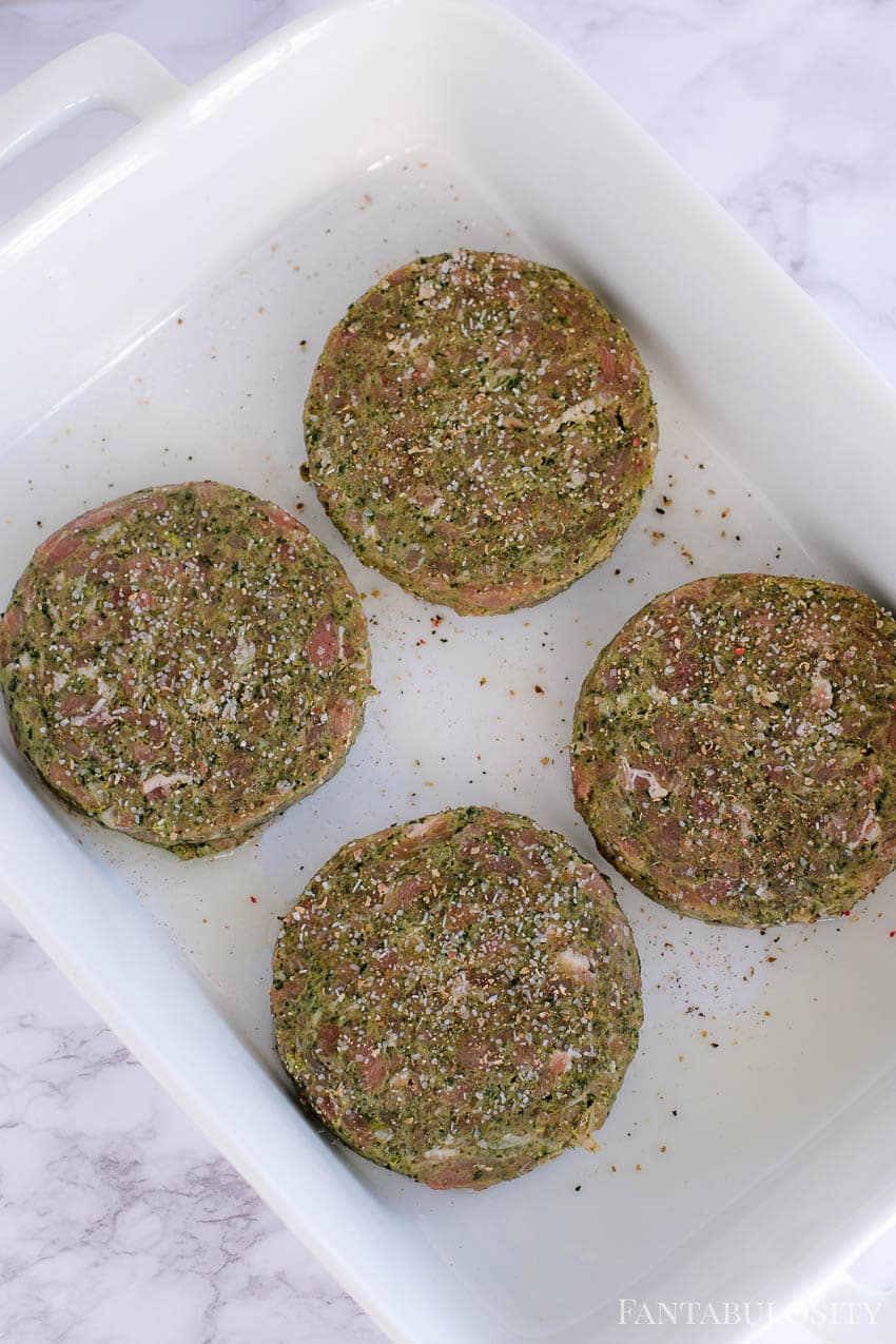 Turkey burgers in white baking dish, seasoned and ready for the oven