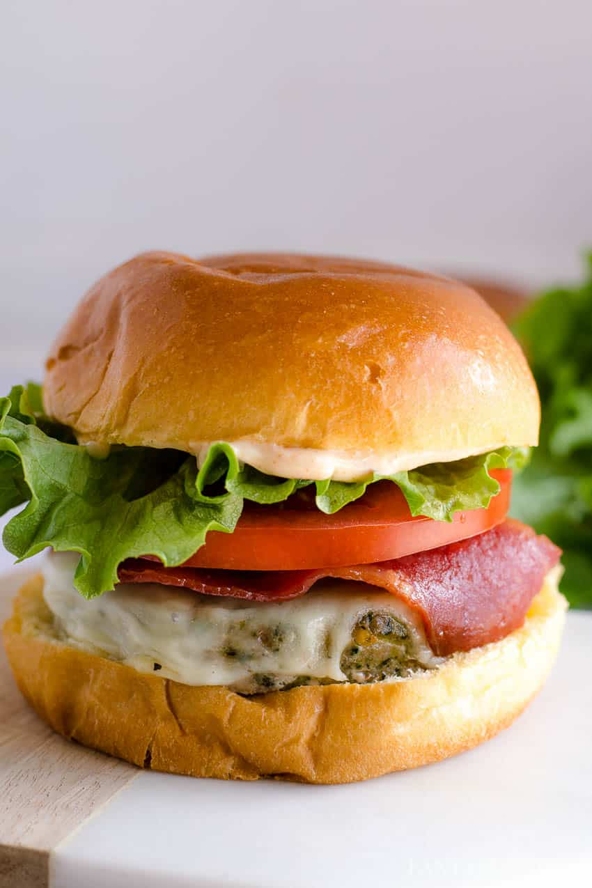 Baked Turkey Burgers on bun with lettuce and tomato and turkey bacon