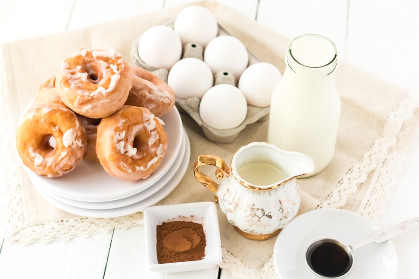 Ingredients on a table to make donut bread pudding - eggs, donuts, milk, cinnamon and more