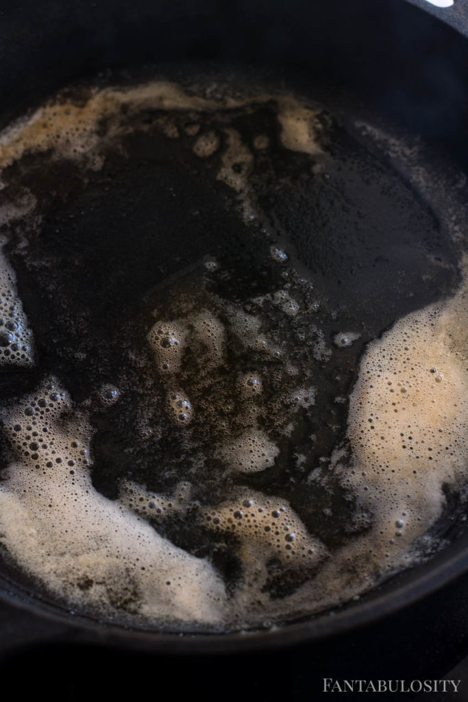 Melted browned butter in cast iron skillet for chicken bites