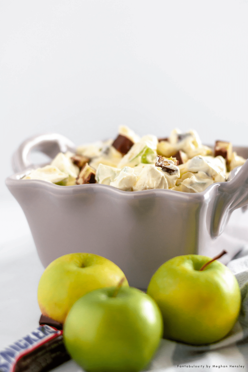 Snicker Apple Salad is the perfect holiday or potluck dish. Crunchy granny smith apples, chunks of snickers and a creamy pudding sauce.