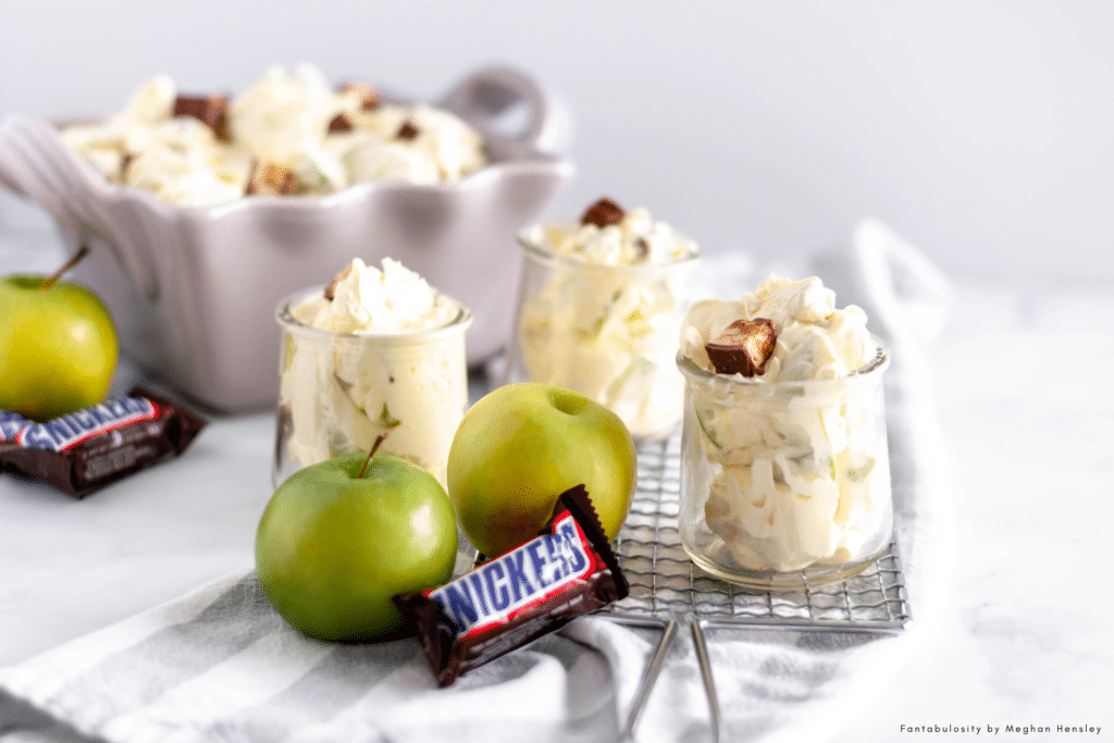 %%page%% Snicker Apple Salad is the perfect holiday or potluck dish. Crunchy granny smith apples, chunks of snickers and a creamy pudding sauce.