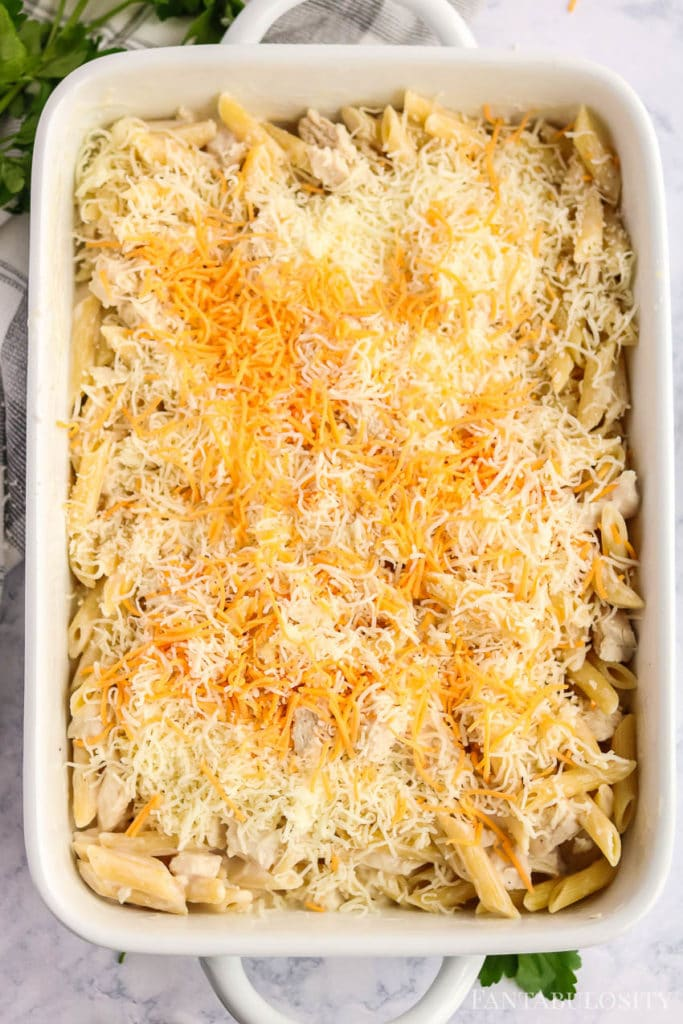 Pasta in a baking dish with cheddar cheese