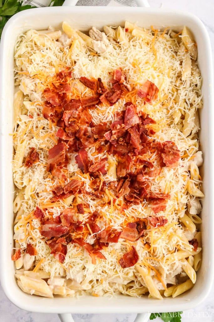Sprinkled bacon on top of chicken bacon ranch pasta in baking dish