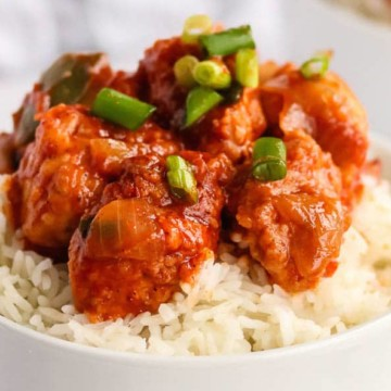Chilli Chicken in a bowl on top of rice with green onions sprinkled on top