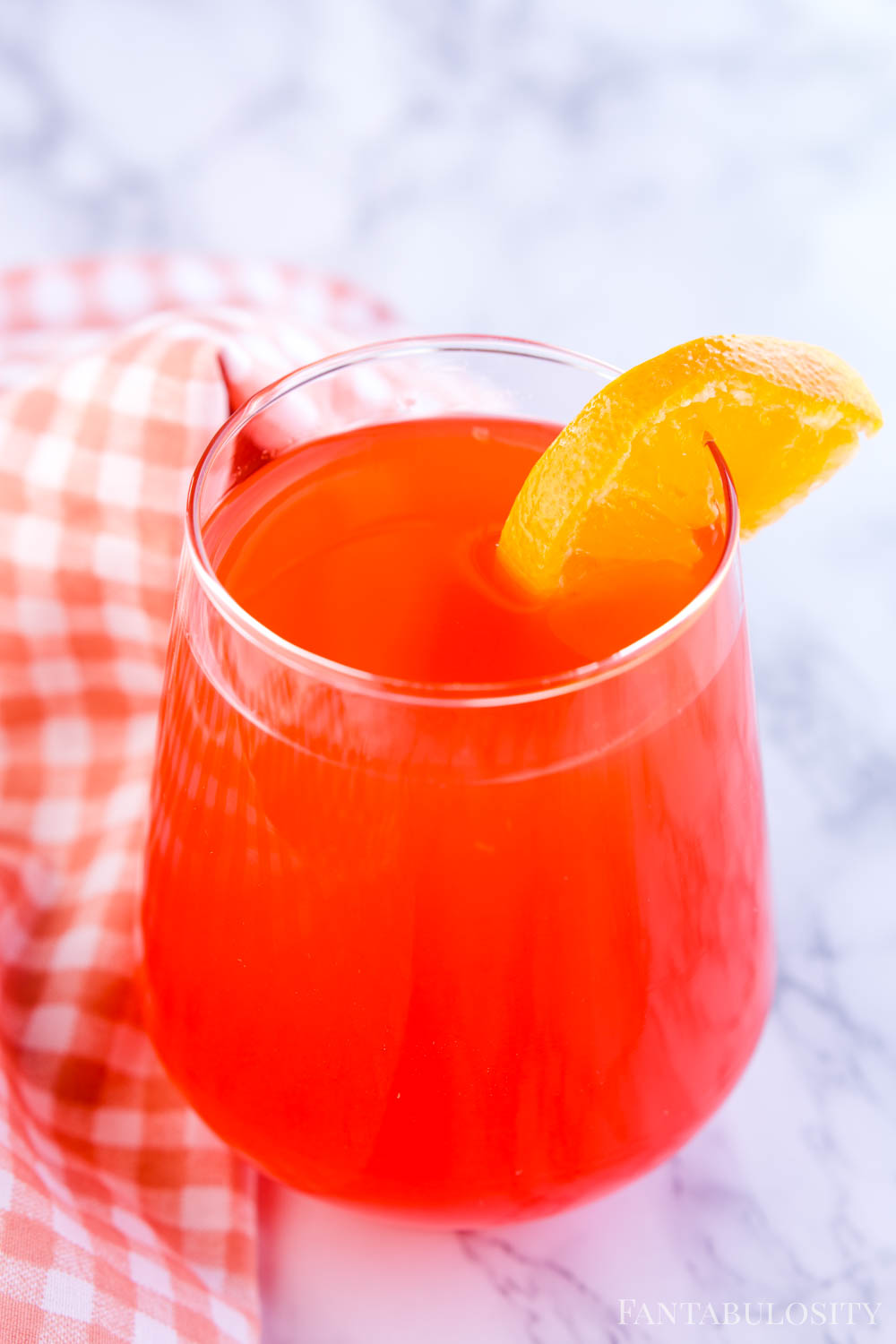 Red Fruit punch in glass with orange slice
