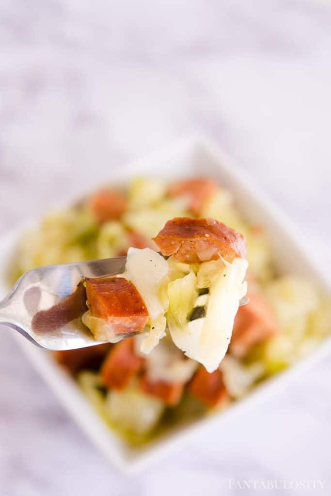 Kielbasa and Cabbage in a white bowl, on a fork