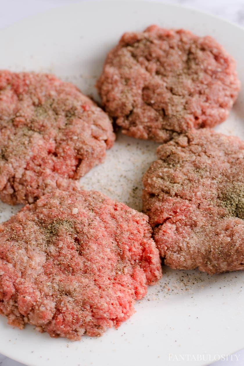 Seasoned hamburger patties with salt and pepper