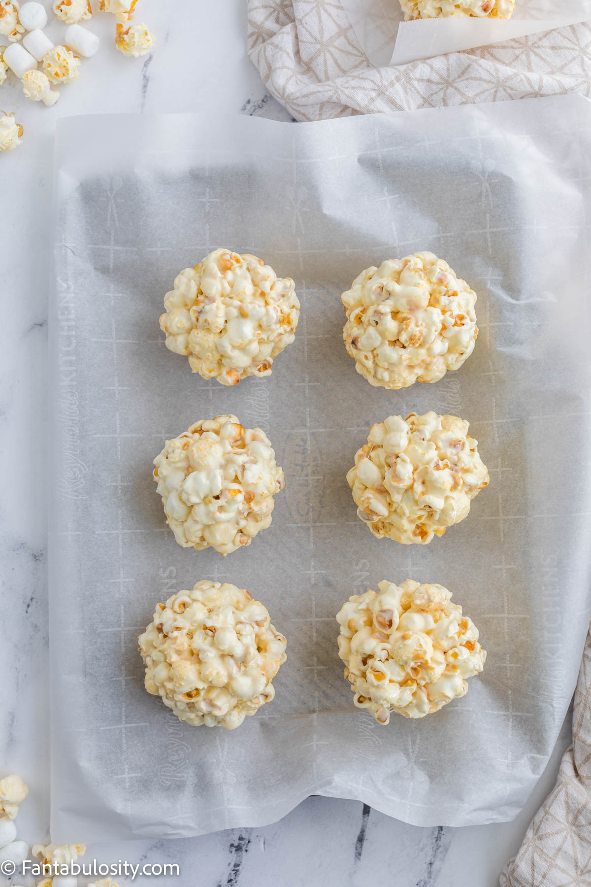 popcorn balls on parchment paper on baking sheet