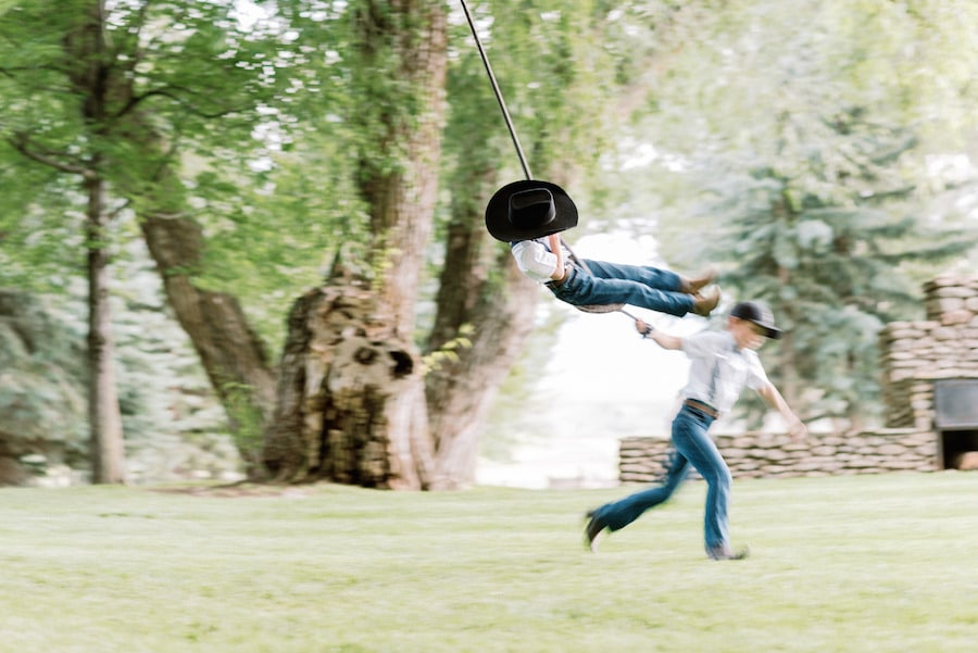 Two little boys playing on rope swing
