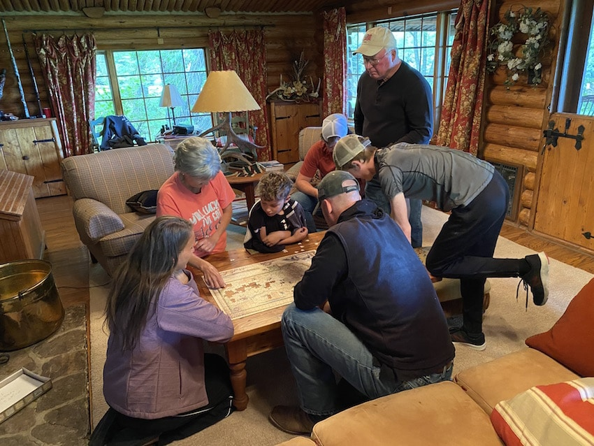 Family around table putting puzzle together