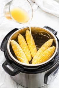 Pour water or stock (broth) in to Instant Pot with corn