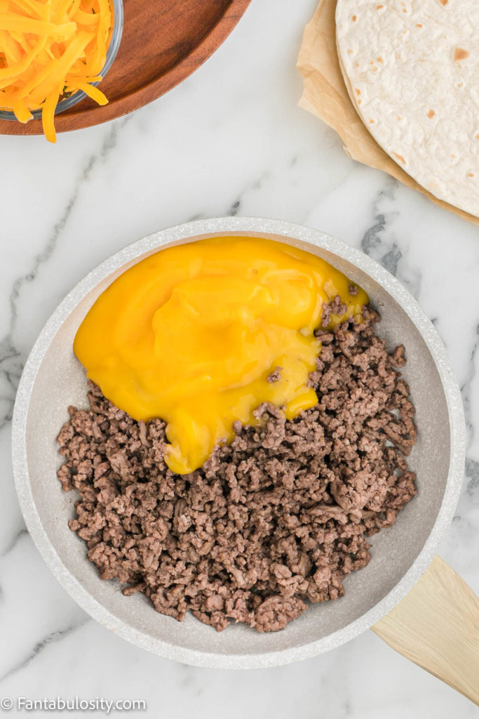 Ground beef and cheddar cheese soup in pan