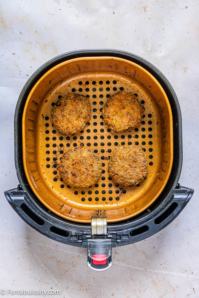 Cooked salmon patties in a single layer in the air fryer basket