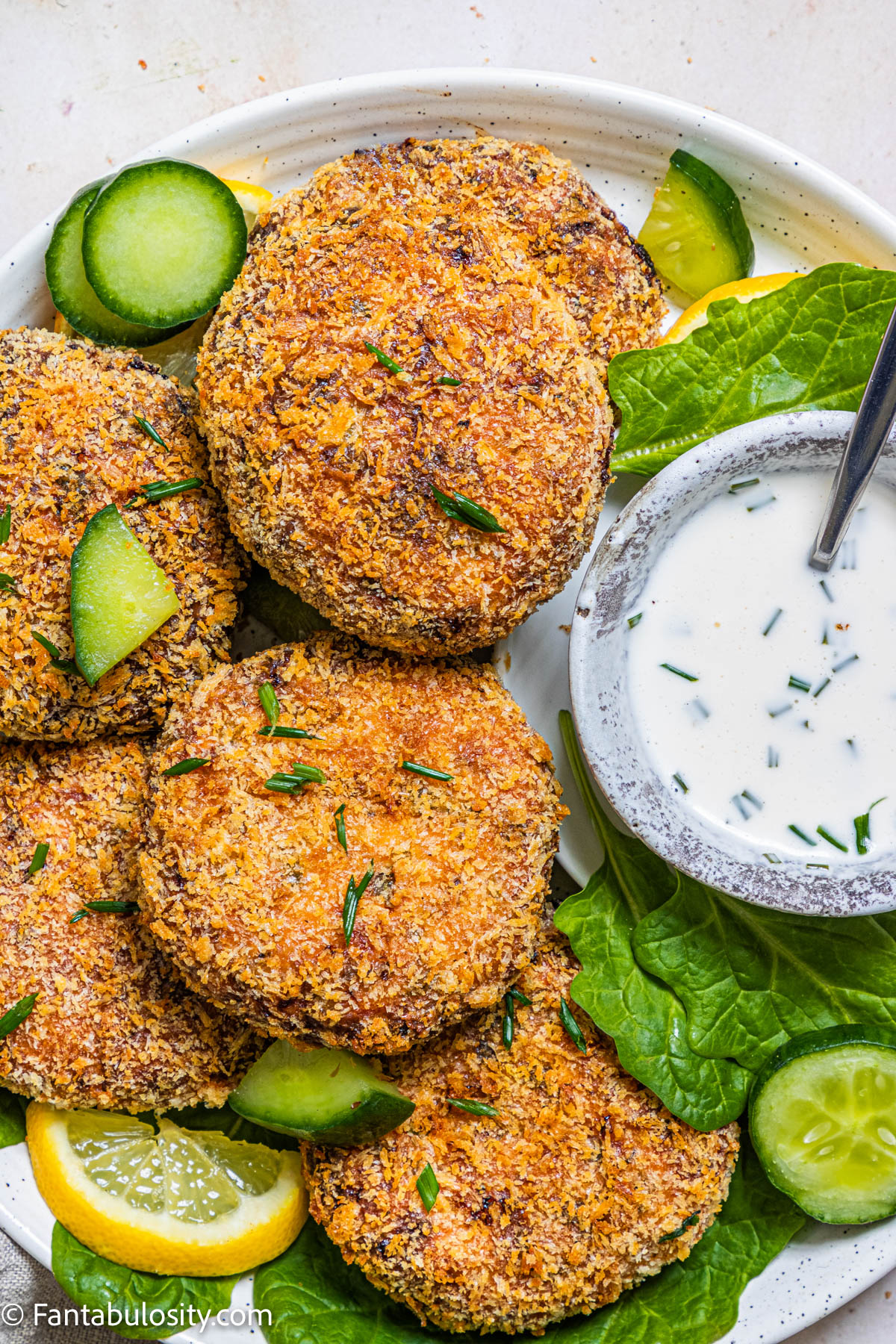 air fryer salmon cakes on plate with dipping sauce and cucumbers