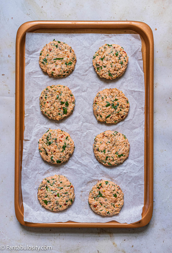 pattied out salmon cakes on parchment paper and baking sheet