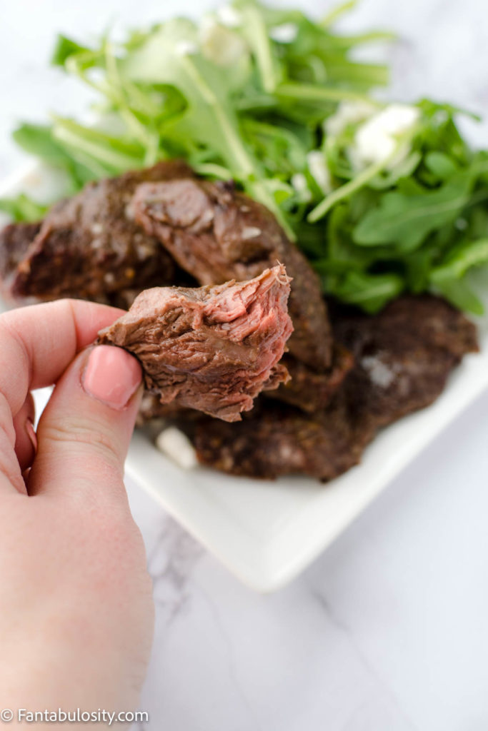 hand holding a piece of air fryer venison to show pink inside