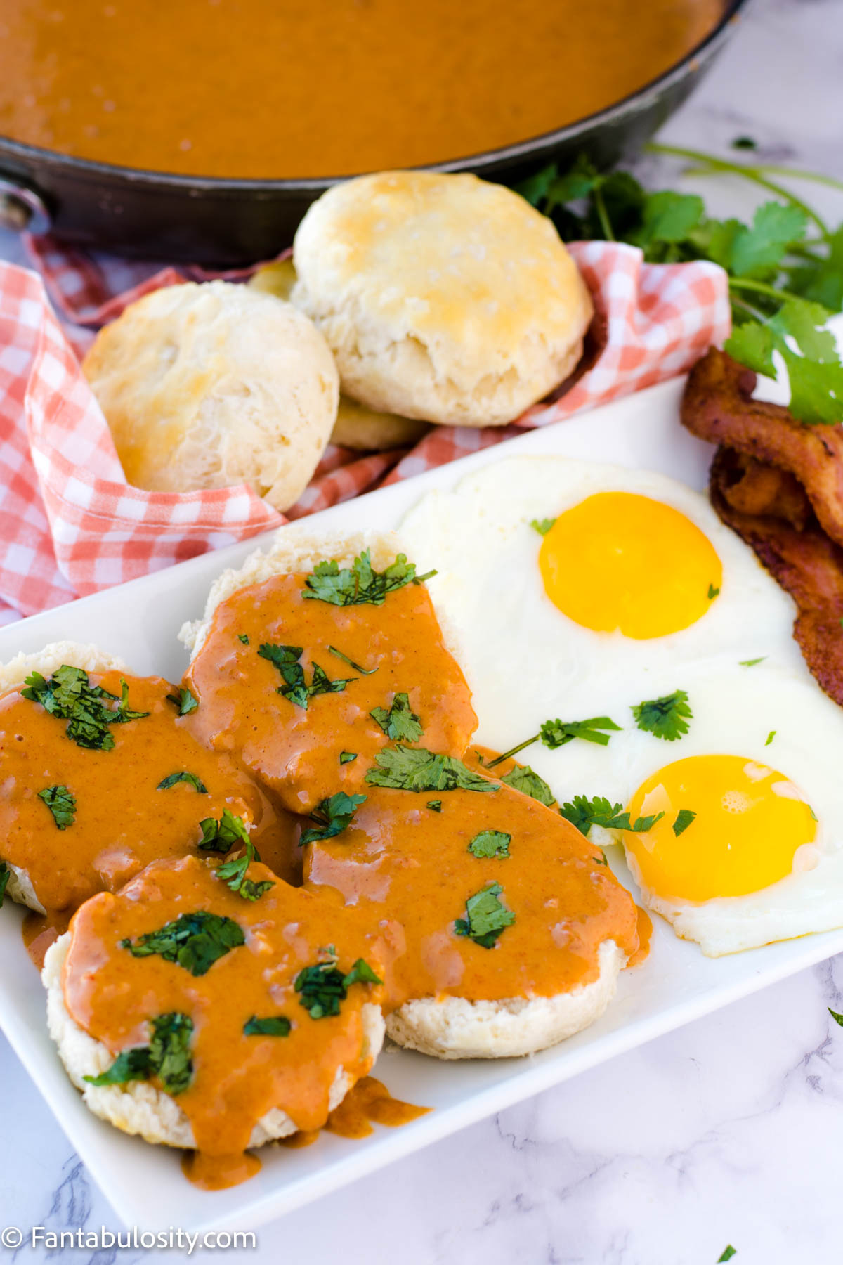 Chorizo gravy on top of biscuits, on a plate with sunny side up eggs, bacon