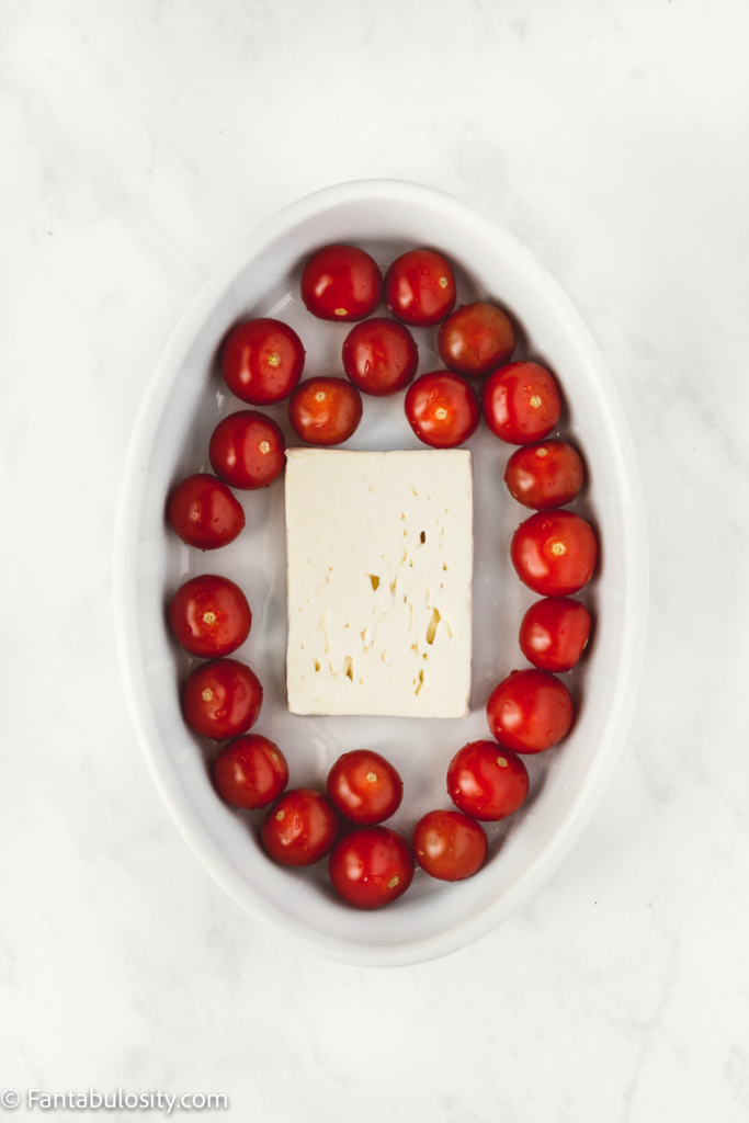 Feta and tomatoes in a baking dish for pasta