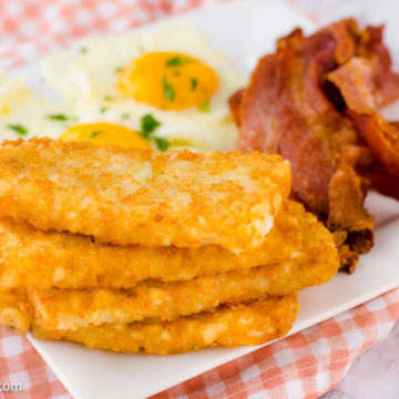 air fryer hash brown patties on white plate with bacon and over easy eggs