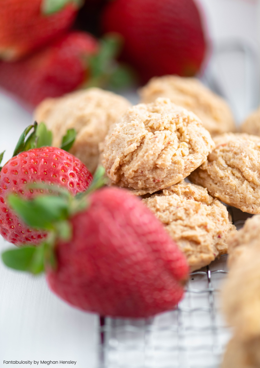Strawberry cheesecake cookies piled up with strawberries surrounding them