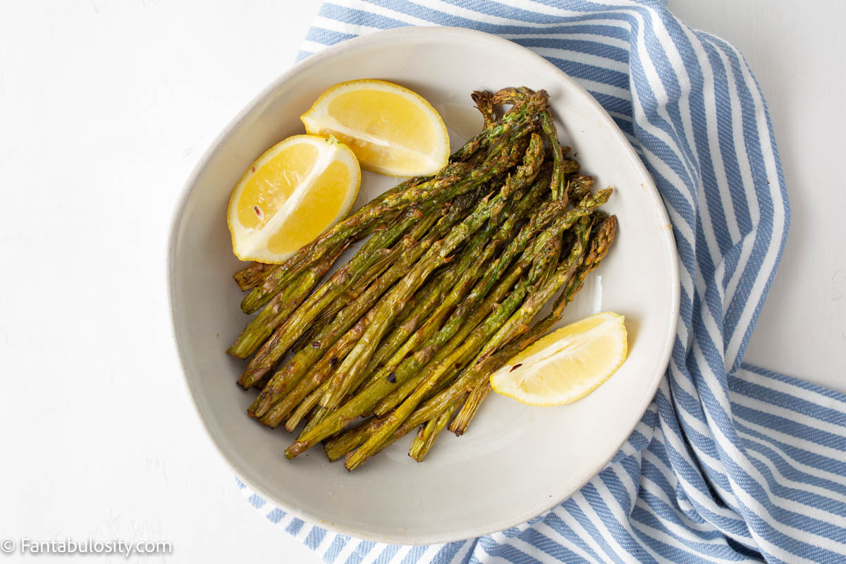 air fryer asparagus with lemon wedges on a white table with blue napkin