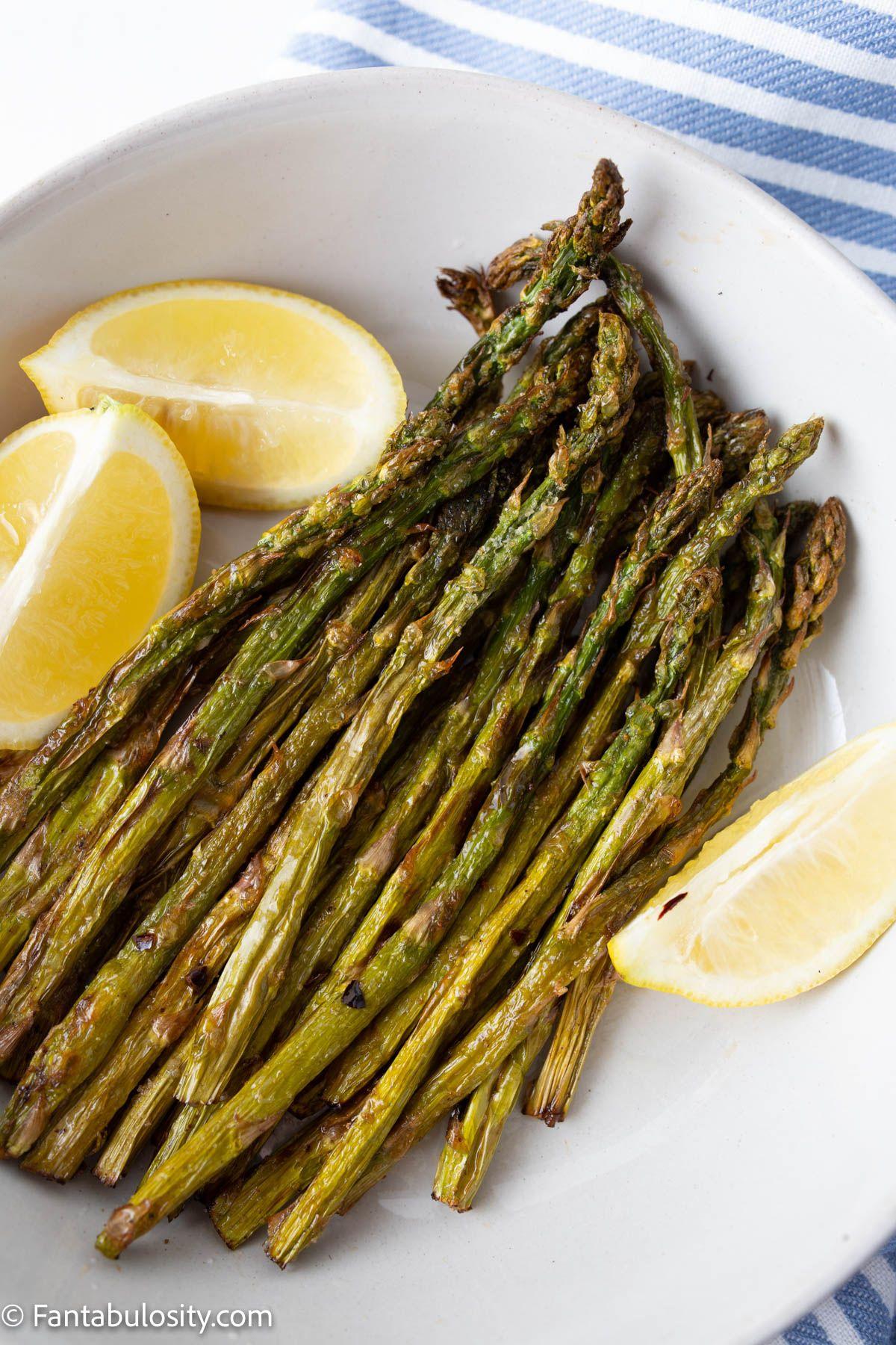 Crispy Air fryer asparagus on a white plate with lemon wedges