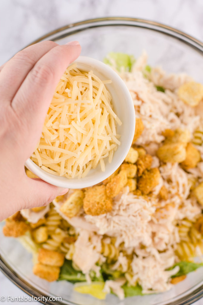 shredded parmesan cheese pouring in to salad
