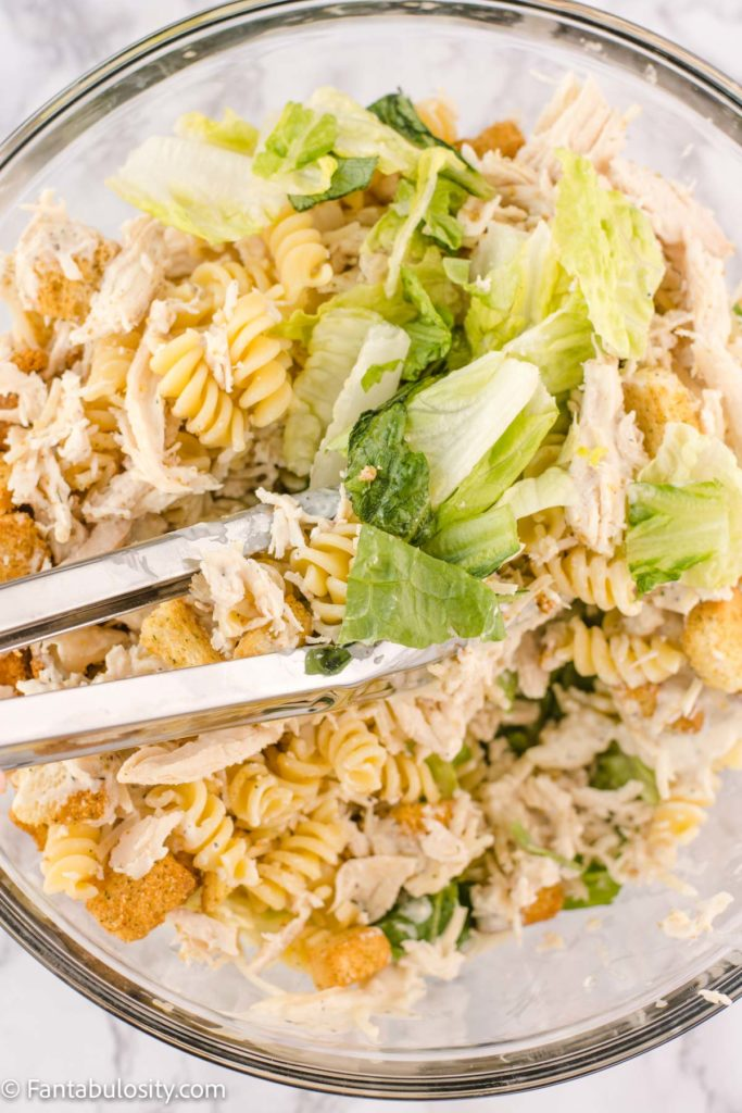 tossing caesar salad with pasta, chicken and dressing