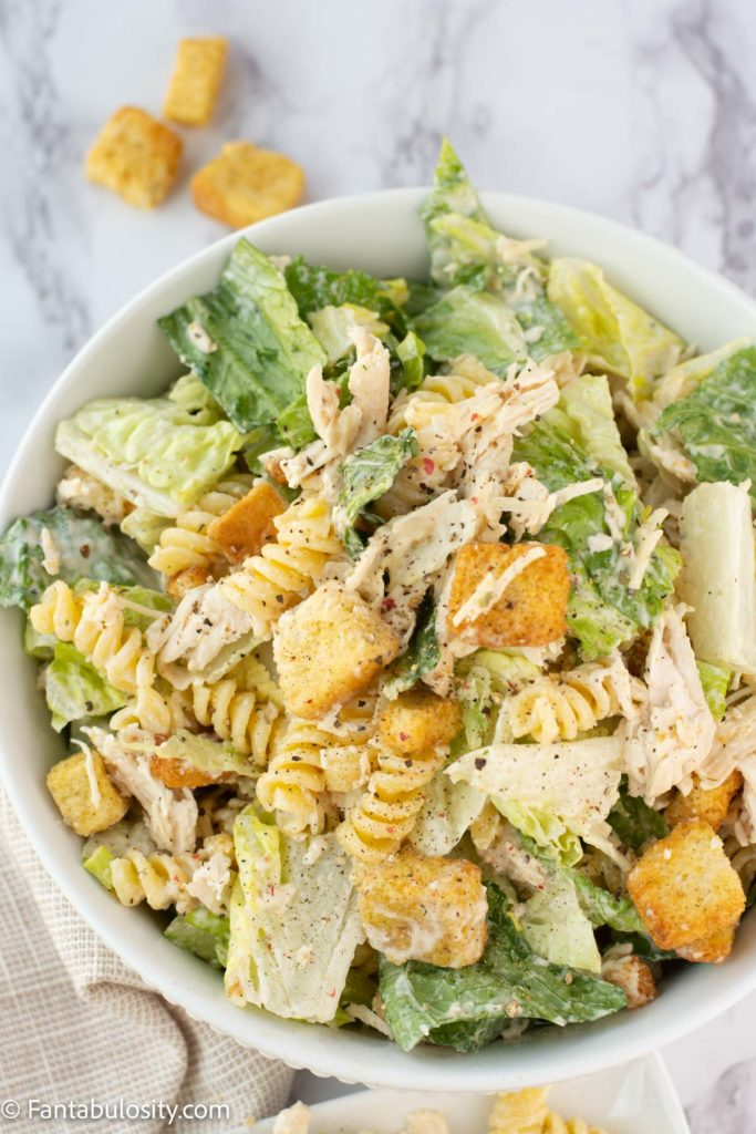 caesar chicken pasta salad recipe in a white bowl on a marble table