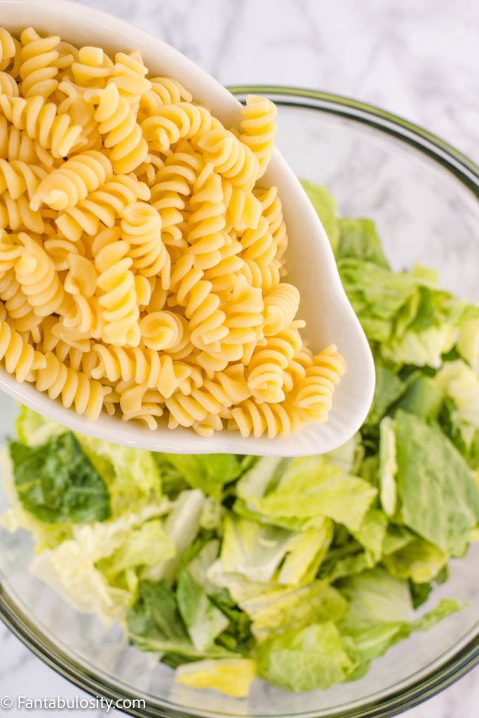 cooked rotini pasta pouring in to lettuce