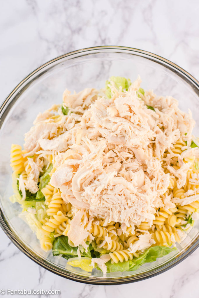 Lettuce, pasta and chicken in large glass bowl