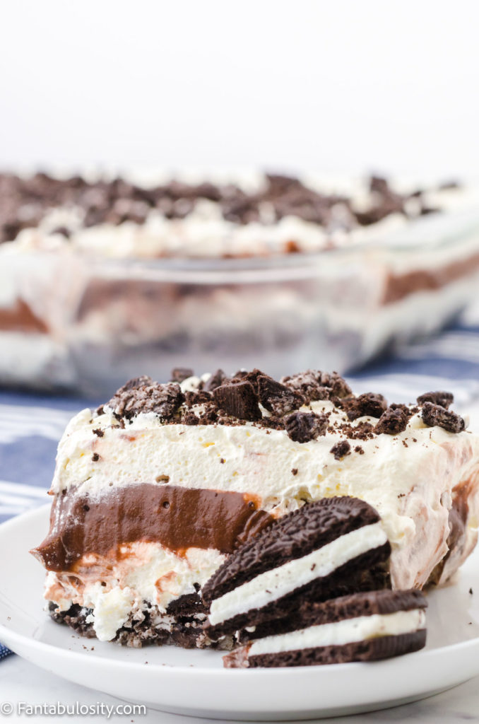 Slice of no bake Oreo dessert on a white plate with cookies