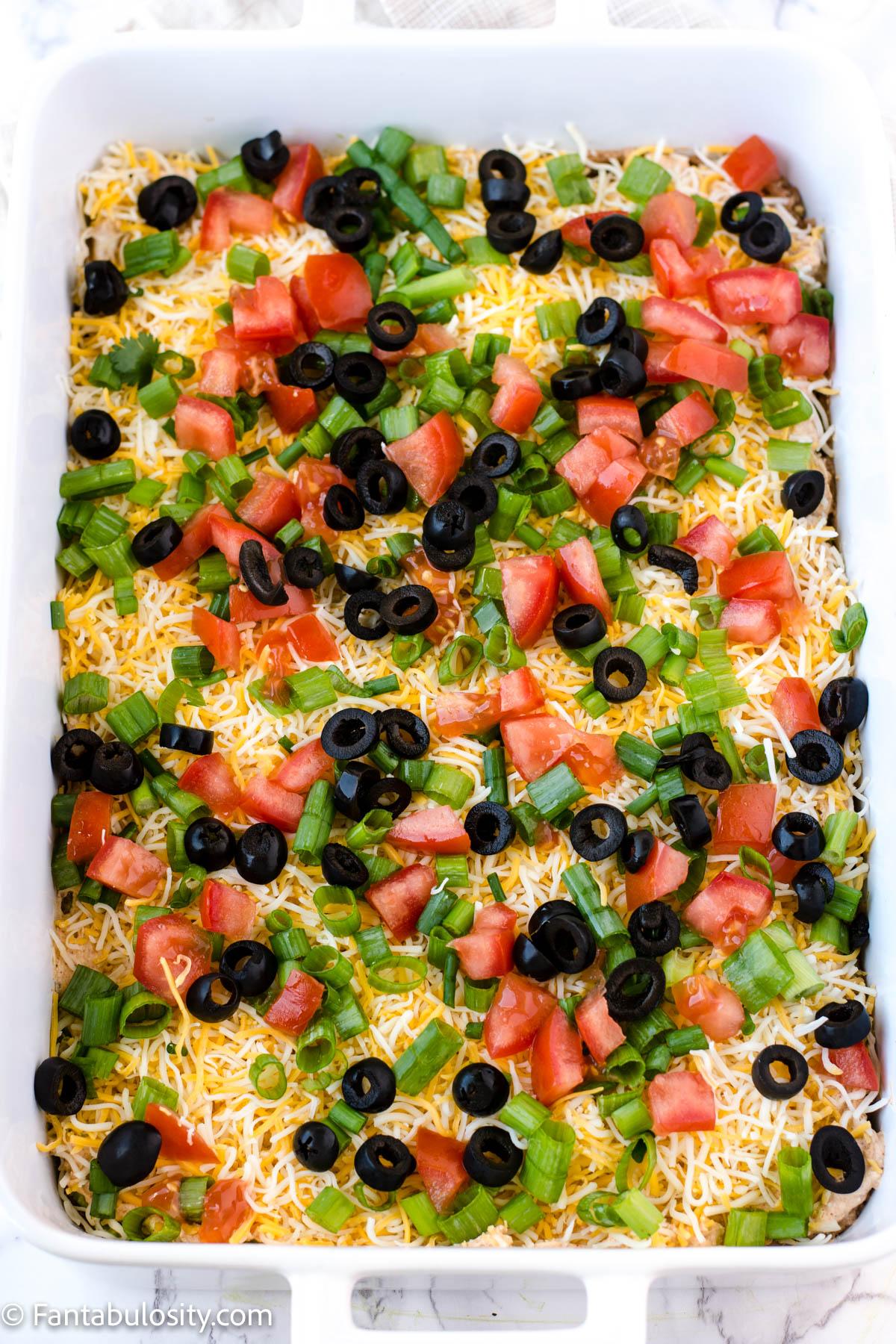 sliced black olives on top of taco dip