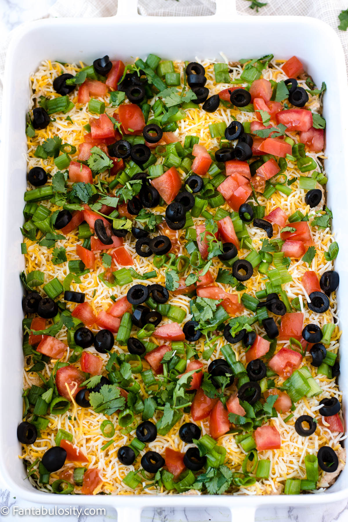 diced fresh cilantro on top of 7 layer taco dip