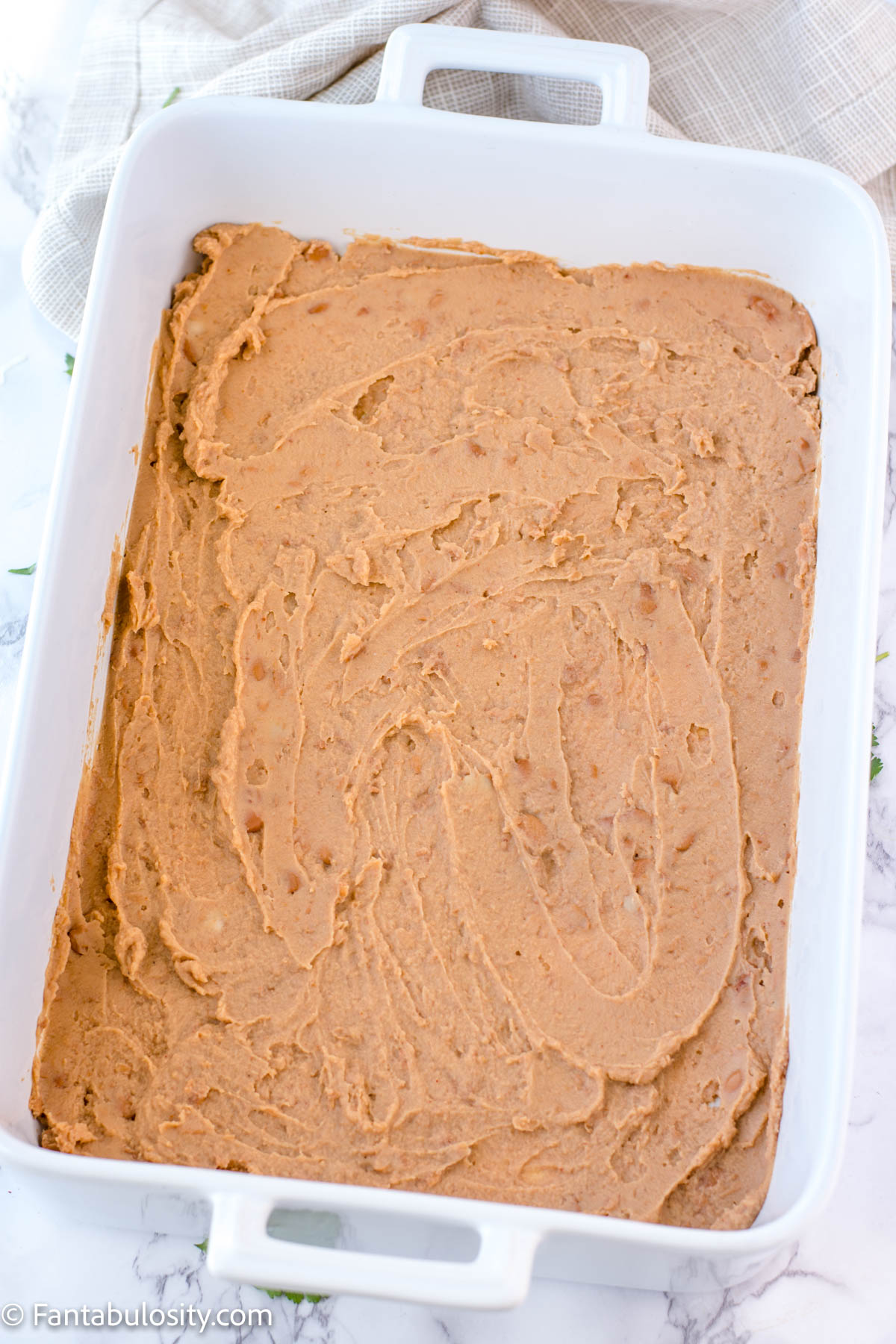 refried beans spread in baking dish