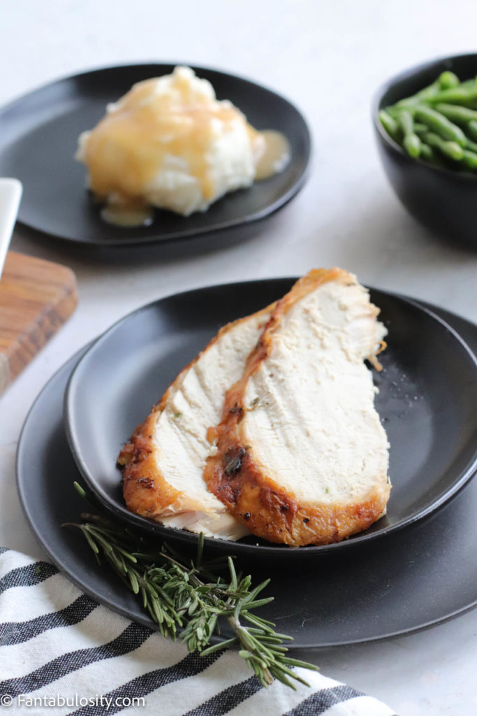 air fryer turkey breast on black plate with side dishes