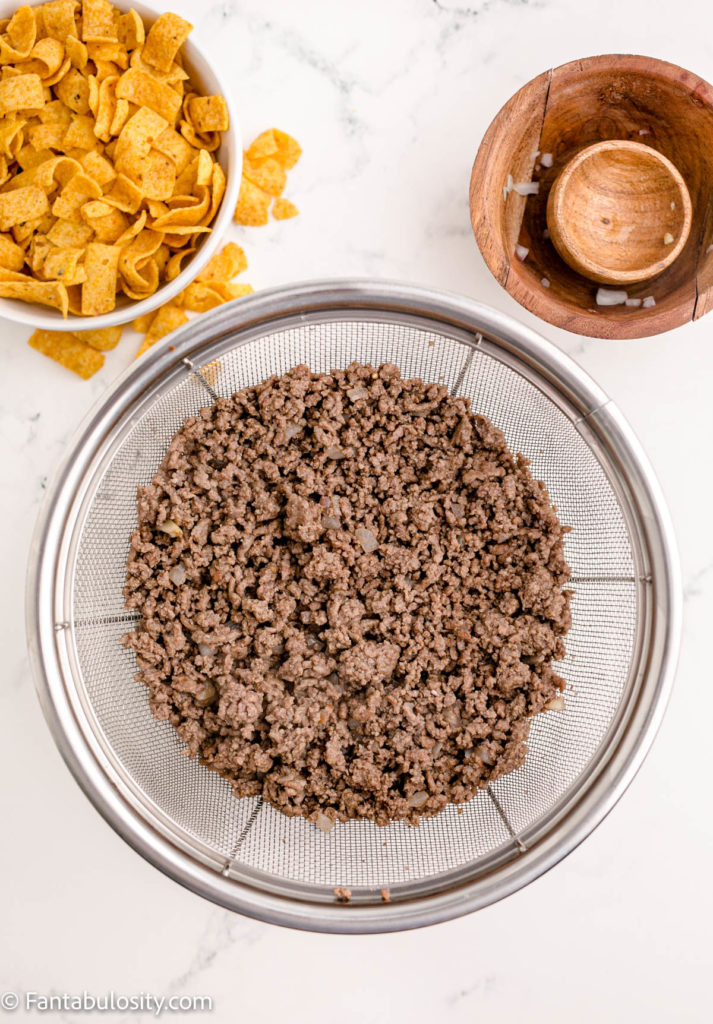Drain cooked ground beef for frito chili pie